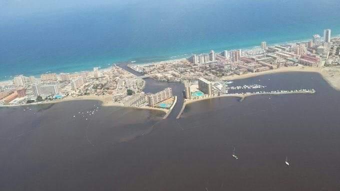 Imagen aérea que permite una comparación entre la calidad de las aguas y que está provocando ese inusitado flujo de veraneantes hacia las playas del Mediterráneo