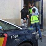 Imagen de los dos detenidos en el momento de ser llevados a la comisaría de policía.