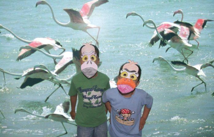 Imagen de dos niños participantes en un taller de máscaras con la imagen de los flamencos del parque Salinas y Arenales de San Pedro del Pinatar.